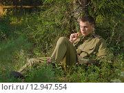 Купить «Солдат сидит на траве и пишет письмо», фото № 12947554, снято 30 июля 2015 г. (c) Дмитрий Черевко / Фотобанк Лори