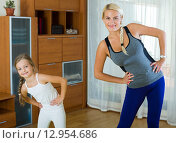 Positive mother and little daughter working out at home. Стоковое фото, фотограф Яков Филимонов / Фотобанк Лори
