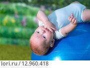 Младенец лежит на синем гимнастическом мяче. Стоковое фото, фотограф Евгений Чернышов / Фотобанк Лори