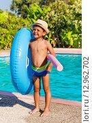 Купить «Мальчик в шляпе стоит возле бассейна с надувным кругом», фото № 12962702, снято 25 июля 2015 г. (c) Сергей Новиков / Фотобанк Лори