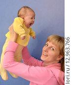 Купить «Веселая молодая женщина поднимает на руках зевающего грудного ребенка», фото № 12963766, снято 19 ноября 2014 г. (c) Ирина Борсученко / Фотобанк Лори