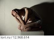 Купить «Концепция психического заболевания. Девушка в рваной белой майке сидит у белой стены», фото № 12968614, снято 16 октября 2015 г. (c) Гурьянов Андрей / Фотобанк Лори