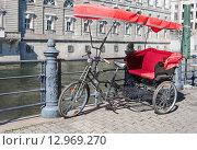 Купить «Пустое велотакси с красной крышей и красным сиденьем в центре  Берлина на набережной Шпрее», фото № 12969270, снято 5 августа 2015 г. (c) Наталья Николаева / Фотобанк Лори