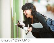 Купить «Multitasking Woman Opening Door», фото № 12977610, снято 20 мая 2019 г. (c) PantherMedia / Фотобанк Лори