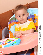 Купить «Маленький ребенок играет в детском кресле», фото № 12984286, снято 26 октября 2015 г. (c) Виктор Топорков / Фотобанк Лори