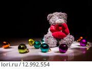 Игрушечный медвежонок с сердечками и елочными шариками на черном фоне. Стоковое фото, фотограф Юлия Добычина/Iuliia Dobychina / Фотобанк Лори