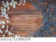 Гвозди и белые лепестки на деревянном столе. Стоковое фото, фотограф Виктор Колдунов / Фотобанк Лори