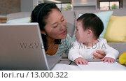 Купить «Mother with baby using laptop », видеоролик № 13000322, снято 10 апреля 2020 г. (c) Wavebreak Media / Фотобанк Лори