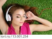 МОлодая девушка слушает музыку в наушниках, лежа на траве. Стоковое фото, фотограф Людмила Дутко / Фотобанк Лори