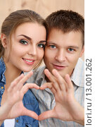 Купить «Счастливая молодая пара показывает жест в виде сердца», фото № 13001262, снято 15 июля 2015 г. (c) Людмила Дутко / Фотобанк Лори