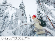 Женщина средних лет с рюкзаком за спиной катается на лыжах в заснеженном лесу. Стоковое фото, фотограф Petri Jauhiainen / Фотобанк Лори