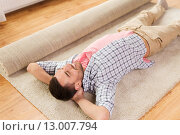 Купить «happy man lying carpet or rug at home», фото № 13007794, снято 6 июня 2015 г. (c) Syda Productions / Фотобанк Лори