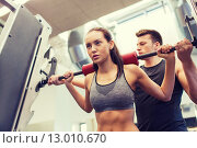 Купить «man and woman with barbell flexing muscles in gym», фото № 13010670, снято 30 ноября 2014 г. (c) Syda Productions / Фотобанк Лори