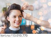 Купить «happy woman with stylist making hairdo at salon», фото № 13010770, снято 15 февраля 2015 г. (c) Syda Productions / Фотобанк Лори