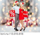 Купить «couple in santa hats with shopping bag over lights», фото № 13010818, снято 3 октября 2015 г. (c) Syda Productions / Фотобанк Лори