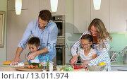 Купить «Attentive parents and their children cooking together », видеоролик № 13011974, снято 23 июля 2019 г. (c) Wavebreak Media / Фотобанк Лори