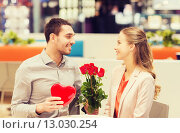 Купить «happy couple with present and flowers in mall», фото № 13030254, снято 10 ноября 2014 г. (c) Syda Productions / Фотобанк Лори
