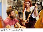 Купить «couple of musicians with guitar at music store», фото № 13030442, снято 11 декабря 2014 г. (c) Syda Productions / Фотобанк Лори