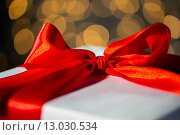 Купить «close up of christmas gift with bow over lights», фото № 13030534, снято 7 октября 2015 г. (c) Syda Productions / Фотобанк Лори