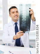 Купить «smiling male doctor in white coat looking at x-ray», фото № 13030834, снято 3 февраля 2015 г. (c) Syda Productions / Фотобанк Лори