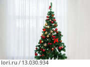 Купить «christmas tree in living room over window curtain», фото № 13030934, снято 8 октября 2015 г. (c) Syda Productions / Фотобанк Лори