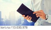 Купить «close up of businessman hands holding open wallet», фото № 13030978, снято 13 ноября 2014 г. (c) Syda Productions / Фотобанк Лори