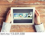 Купить «close up of hands with video gallery on tablet pc», фото № 13031030, снято 10 октября 2014 г. (c) Syda Productions / Фотобанк Лори