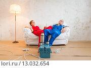 Ремонт в квартире, мужчина и женщина в рабочей одежде сидят на диване. Стоковое фото, фотограф Petri Jauhiainen / Фотобанк Лори