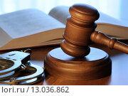 Купить «Судейский молоток, уголовный кодекс и наручники лежат на столе», фото № 13036862, снято 30 октября 2015 г. (c) Денис Ларкин / Фотобанк Лори