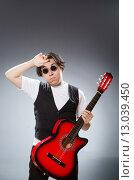 Купить «Funny guitar player in musical concept», фото № 13039450, снято 28 июня 2015 г. (c) Elnur / Фотобанк Лори