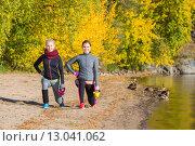 Две симпатичные молодые подруги с гирями занимаются фитнесом на природе. Стоковое фото, фотограф Petri Jauhiainen / Фотобанк Лори