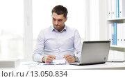 Купить «busy businessman with laptop and papers in office», видеоролик № 13050834, снято 8 июля 2015 г. (c) Syda Productions / Фотобанк Лори