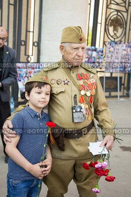 Ветеран Великой Отечественной войны общается с мальчиком. 9 мая 2015 года