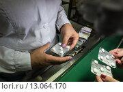 Блистеры с таблетками в руках. Фармацевтическая компания Vertex, Санкт-Петербург (2015 год). Редакционное фото, фотограф Игорь Акимов / Фотобанк Лори