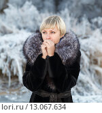 Купить «Девушка со светлыми волосами и короткой стрижкой в черном пальто с меховым воротником», фото № 13067634, снято 19 июля 2018 г. (c) Mikhail Starodubov / Фотобанк Лори