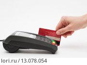 Терминал для безналичной оплаты и рука, проводящая банковскую карту по магнитному считывателю. Стоковое фото, фотограф Константин Колосов / Фотобанк Лори