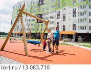 Купить «Счастливая семья стоит  во дворе нового дома, на детской площадке», фото № 13083710, снято 25 июня 2015 г. (c) Алексей Маринченко / Фотобанк Лори