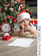Купить «Мечтательная девочка пишет письмо Деду Морозу около елки», фото № 13097862, снято 2 ноября 2013 г. (c) Оксана Гильман / Фотобанк Лори