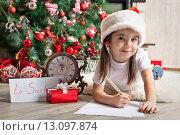 Купить «Задумчивая девочка пишет письмо Деду Морозу», фото № 13097874, снято 2 ноября 2013 г. (c) Оксана Гильман / Фотобанк Лори