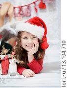 Купить «Smiling girl in a Santa hat», фото № 13104710, снято 6 января 2014 г. (c) Ingram Publishing / Фотобанк Лори