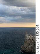 """Купить «Замок """"Ласточкино гнездо"""" на фоне вечернего моря и хмурые осенние облака», эксклюзивное фото № 13135654, снято 9 октября 2015 г. (c) Яна Королёва / Фотобанк Лори"""