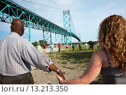 Detroit, Michigan - Community activists in southwest Detroit join hands to celebrate after tearing down a fence blocking access to part of Riverside Park... Стоковое фото, фотограф Jim West / age Fotostock / Фотобанк Лори