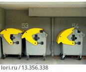 Купить «Drei fahrbare Restmüll_Container mit gelben Deckeln _ unterschiedlich weit geöffnet _ im Hintergrund die Zahlen 53 und 54 für die Wohneinheiten und ein Abflussrohr in grau.», фото № 13356338, снято 18 апреля 2019 г. (c) age Fotostock / Фотобанк Лори