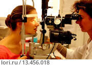 Купить «Ophthalmologist carrying out an examination opthtalmologic using a slit_lamp. This instrument shines a fine beam of light into the eye, and magnifying...», фото № 13456018, снято 12 декабря 2017 г. (c) age Fotostock / Фотобанк Лори
