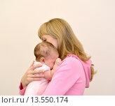 Купить «Молодая женщина обнимает плачущего грудного ребенка», фото № 13550174, снято 19 ноября 2014 г. (c) Ирина Борсученко / Фотобанк Лори