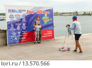 Купить «Уличный фотограф на набережной в Севастополе», фото № 13570566, снято 14 июля 2015 г. (c) Ивашков Александр / Фотобанк Лори