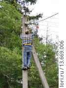 Купить «Электромонтер на столбе чинит электросеть в дачном поселке», эксклюзивное фото № 13669006, снято 13 июля 2015 г. (c) Елена Коромыслова / Фотобанк Лори