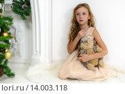Нарядная девочка сидит на полу с игрушкой в новогоднем интерьере. Стоковое фото, фотограф Максим Тимофеев / Фотобанк Лори