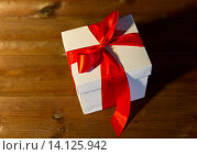 Купить «close up of christmas gift box on wooden floor», фото № 14125942, снято 1 октября 2015 г. (c) Syda Productions / Фотобанк Лори