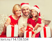 Купить «smiling family holding gift boxes and sparkles», фото № 14139534, снято 26 октября 2013 г. (c) Syda Productions / Фотобанк Лори